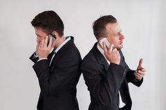 The businessmen speaking by phone on a white background. Businessman talking having conversation on mobile phone, speaking on cellphone, business men using cell Royalty Free Stock Photo