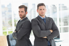 Businessmen standing with arms crossed in office Royalty Free Stock Photo