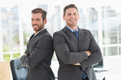 Businessmen standing with arms crossed in office Stock Image