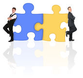 Businessmen standing back to back on puzzle. Two businessmen in different suits standing back to back leaning on puzzle shape collage Stock Images