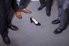 Businessmen standing in a circle around a woman's high heel, feet and legs only Royalty Free Stock Image