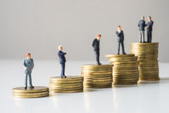 Businessmen standing on coins stack. Royalty Free Stock Photography