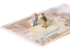 Businessmen standing on euro banknotes, financial deal concept Stock Images