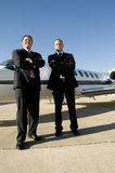 Businessmen standing in front of corporate jet. Young businessmen looking to the distance in front of corporate jet Stock Images