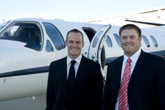 Businessmen standing in front of corporate jet. Businessmen smiling in front of their corporate jet Royalty Free Stock Image