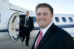 Businessmen standing in front of corporate jet. Young businessmen in front of their corporate jet. Focus on the man in front Stock Images