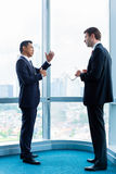Businessmen standing in front of office window Stock Photos