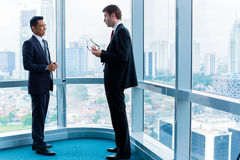 Businessmen standing in front of office window Royalty Free Stock Photography