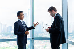 Businessmen standing in front of office window Royalty Free Stock Images