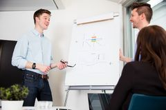 Businessmen Standing By Presentation Board In Office Stock Photos