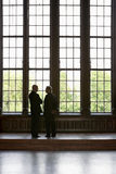 Businessmen Standing By Tall Windows Stock Photography