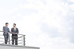 Businessmen standing at terrace railings against cloudy sky Stock Image