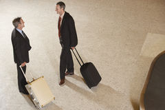 Businessmen With Suitcases By Luggage Carousel In Airport Royalty Free Stock Photo