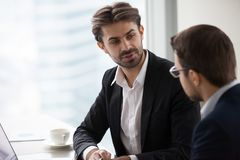 Businessmen in suits discuss business ideas in office stock photos