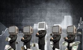 Modern technologies against old one. Businessmen in suits with old TV instead of their heads keeping arms crossed while standing in a row and one at the head Royalty Free Stock Image