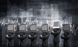 Modern technologies against old one. Businessmen in suits with old TV instead of their heads keeping arms crossed while standing in a row and one at the head Stock Photography