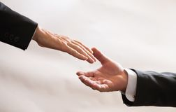 Businessmen in suits reach out to each other for handshake, help, deal, Finance Royalty Free Stock Photos