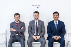 Businessmen in suits sitting on chairs at white waiting room Stock Photography