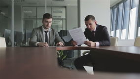 Businessmen in suits and ties discuss a case sitting at a table. Meeting business partners in a meeting room. Work with a documents. Signing a contract stock footage