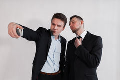The businessmen taking a selfie on white background. The businessmen taking a selfie from phone on a white background Royalty Free Stock Images