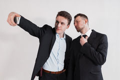 The businessmen taking a selfie on white background. The businessmen taking a selfie from phone on a white background Stock Photo