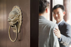 Businessmen Talking Behind Open Door Royalty Free Stock Image