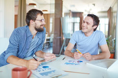Businessmen talking. Image of two young businessmen interacting at meeting in office Stock Images
