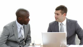 Businessmen talking in a meeting. AfroAmerican and caucasian young businessmen talking in a meeting and working with a laptop. Footage in High definition stock video footage