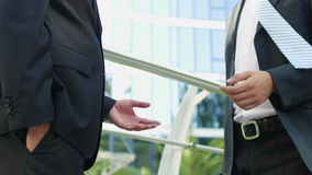 Businessmen talking near the office building stock footage