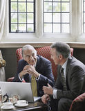 Businessmen Talking Over Laptop In Lobby Royalty Free Stock Photo