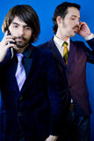 Businessmen talking on phones. Two businessmen talking on their mobile phones, over a blue background Royalty Free Stock Images