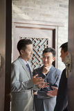 Businessmen Talking and Smiling in Doorway Royalty Free Stock Photography