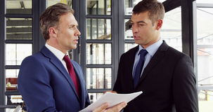 Businessmen talking together while looking folder stock footage