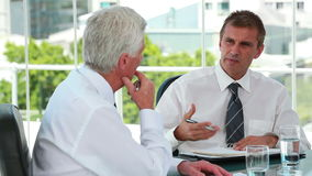 Businessmen talking together while sitting. At a meeting table stock footage