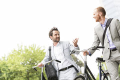 Businessmen talking while walking with bicycles outdoors Stock Photo
