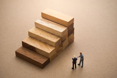 Businessmen talking about wood block step. Stock Images