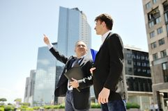 Businessmen talking about work project on background modern office corporate buildings. Two businessmen talking about work project on background modern office Stock Photo