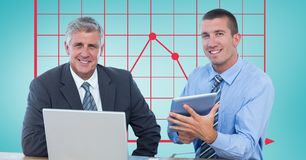 Businessmen with technologies against graph Royalty Free Stock Photo