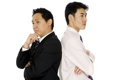 Businessmen Thinking. Two young asian businessmen standing back to back and thinking Royalty Free Stock Photography