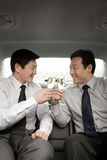 Businessmen toasting in back of car Stock Photography