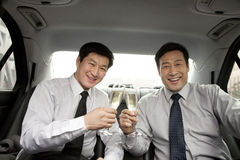 Businessmen toasting in back of car Royalty Free Stock Photo