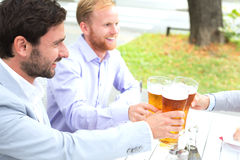 Businessmen toasting beer glasses with female colleague at outdoor restaurant Stock Photography