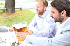 Businessmen toasting beer glasses with female colleague at outdoor restaurant Stock Photo