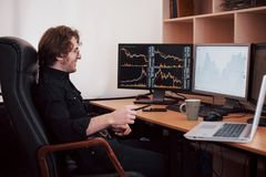 Businessmen trading stocks online. Stock broker looking at graphs, indexes and numbers on multiple computer screens. Business success concept stock image