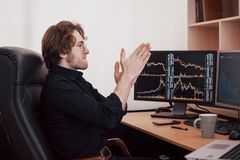 Businessmen trading stocks online. Stock broker looking at graphs, indexes and numbers on multiple computer screens. Business success concept stock images