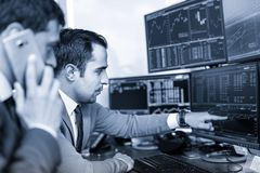 Stock brokers trading online in corporate office. Businessmen trading stocks online. Stock brokers looking at graphs, indexes and numbers on multiple computer Royalty Free Stock Photos
