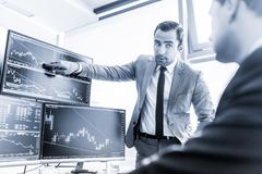 Stock brokers trading online in corporate office. Stock Photography