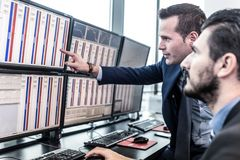 Stock traders looking at market data on computer screens. Businessmen trading stocks. Stock traders looking at charts, indexes and numbers on multiple computer Stock Photos