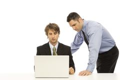 Businessmen use a laptop. Businessmen talk while using a laptop computer Royalty Free Stock Photo