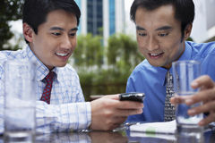 Businessmen Using Cell Phone At Outdoor Cafe Royalty Free Stock Image